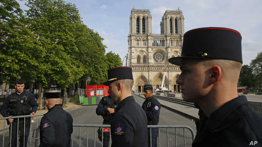Members of Paris Firefighters' brigade enter the security perimeter to Notre Dame cathedral in Paris, April 18, 2019. France paid a daylong tribute Thursday to the Paris firefighters who saved Notre Dame Cathedral from collapse.