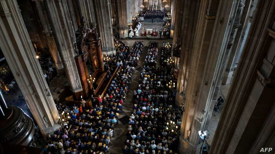 A general view shows people attending Mass in tribute to the Notre-Dame de Paris Cathedral at the Saint Eustache church in Paris on Easter Sunday, April 21, 2019.
