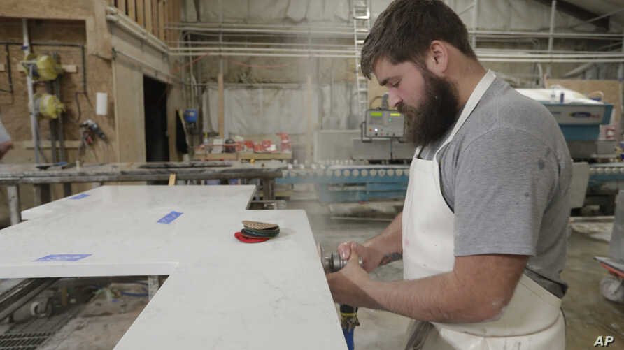 C.J. Haskett polishes the edge of a kitchen countertop cut from imported quartz slabs from China in the production facility at Marble Uniques in Tipton, Ind., May 3, 2019.