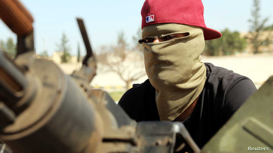 A masked member of Libyan internationally recognized pro-government forces is seen in a military vehicle on the outskirts of Tripoli, Libya, April 10, 2019.