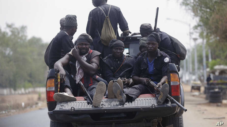 Vigilantes and local hunters armed with locally made guns patrol on the street near the Independent National Electoral Commission office in Yola, Nigeria, Feb. 25, 2019.
