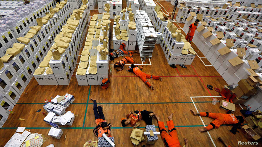 Workers lay during a break as they prepare election materials before their distribution to polling stations in a warehouse in Jakarta, Indonesia, April 15, 2019.