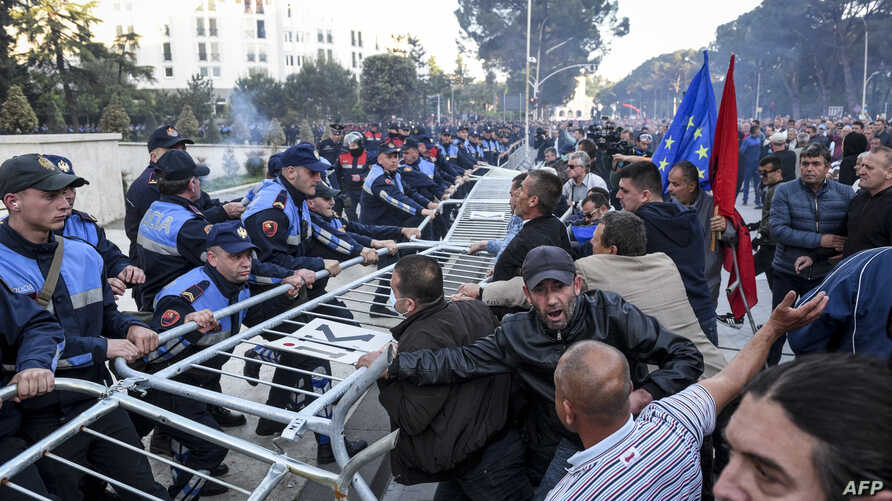Demonstrators try to remove a metal fence outside a government building during an opposition protest  in Tirana, Albania, May 11, 2019.