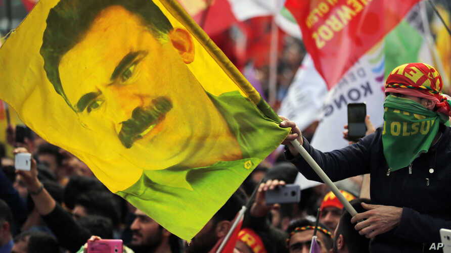 FILE - A youth holds a flag with the image of Abdullah Ocalan, the jailed leader of the rebel Kurdistan Workers' Party, or PKK, in Istanbul, Turkey, March 21, 2018.