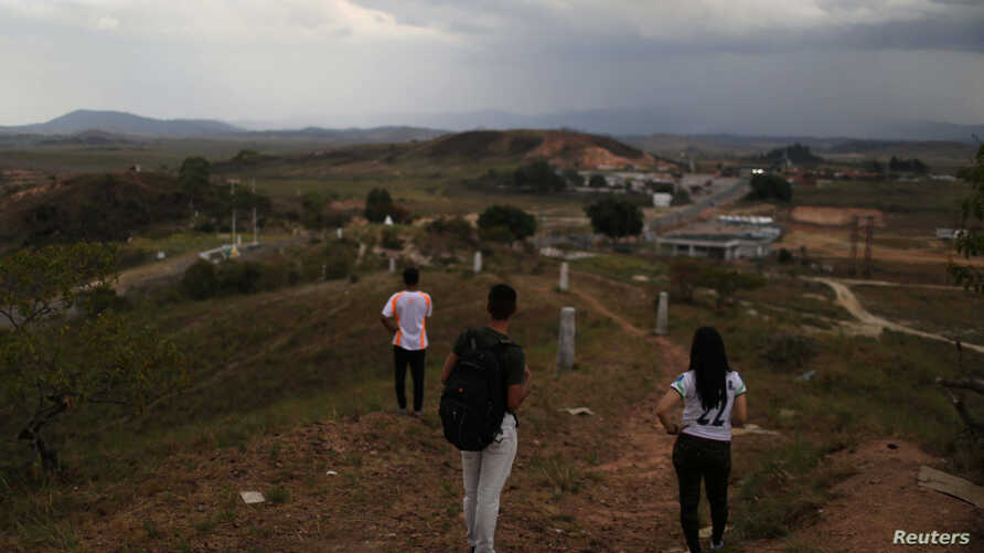 FILE - Venezuelan military deserters of the National Guard, who don't want to be identified, stand at the border point with Venezuela, in Pacaraima, Brazil, April 11, 2019.