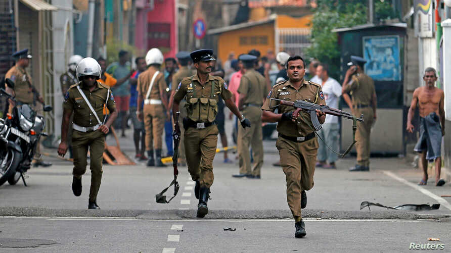 Sri Lankan police clear the area while Special Task Force Bomb Squad officers inspect the site of an exploded van near a church that was attacked yesterday in Colombo, April 22, 2019.