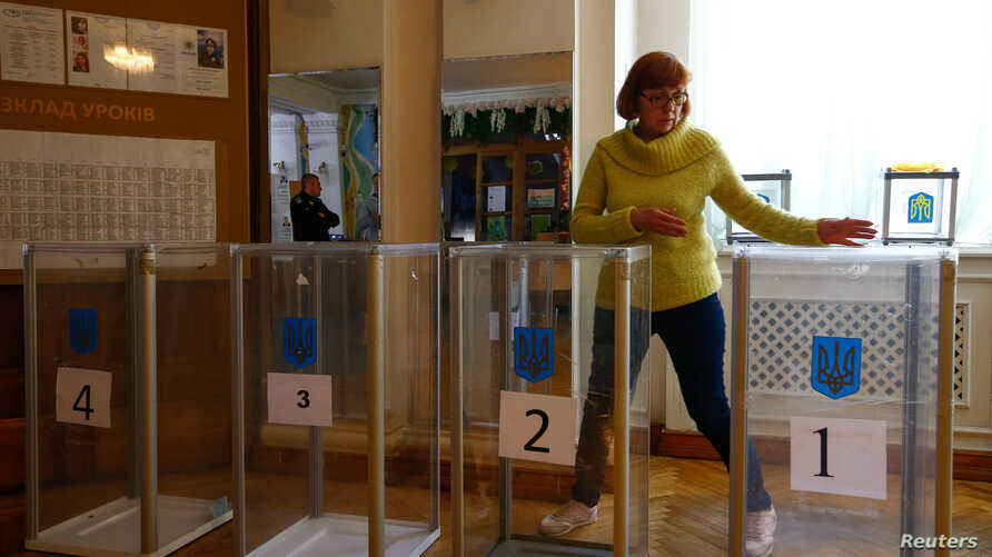 A member of a local electoral commission takes part in preparations for the upcoming presidential election at a polling station in Kyiv, Apr. 20, 2019.
