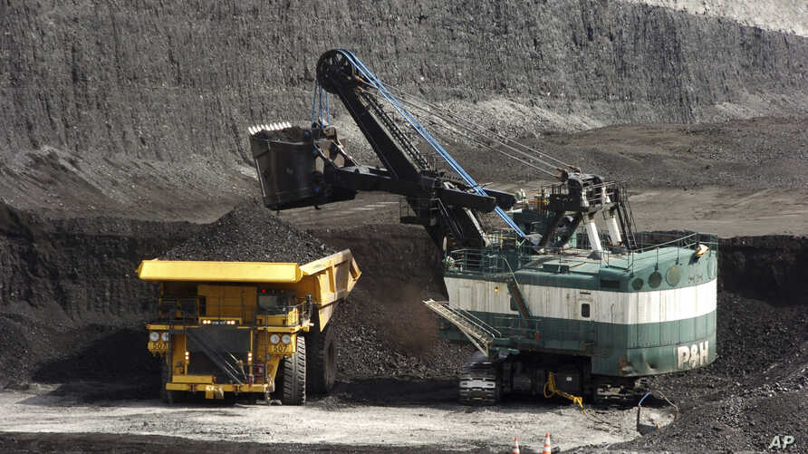 FILE - A mechanized shovel loads a haul truck with coal at the Spring Creek coal mine near Decker, Mont., April 4, 2013. A federal judge in Montana says the Trump administration failed to consider the environmental effects of resuming coal sales from...
