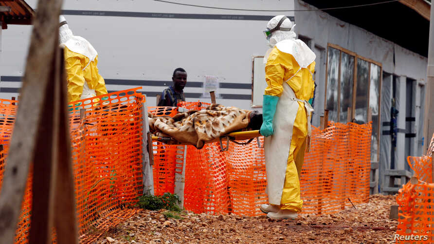 FILE - Health workers carry a newly admitted confirmed Ebola patient into a treatment centre in Butembo in the eastern Democratic Republic of Congo, March 28, 2019.
