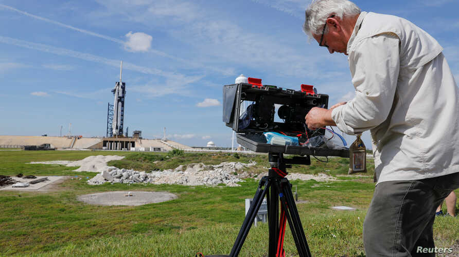 Photographer Thom Baur installs remote cameras around the Crew Drago spacecraft as it sits on launch pad 39A before the uncrewed test flight to the International Space Station from the Kennedy Space Center in Cape Canaveral, Fla., March 1, 2019.