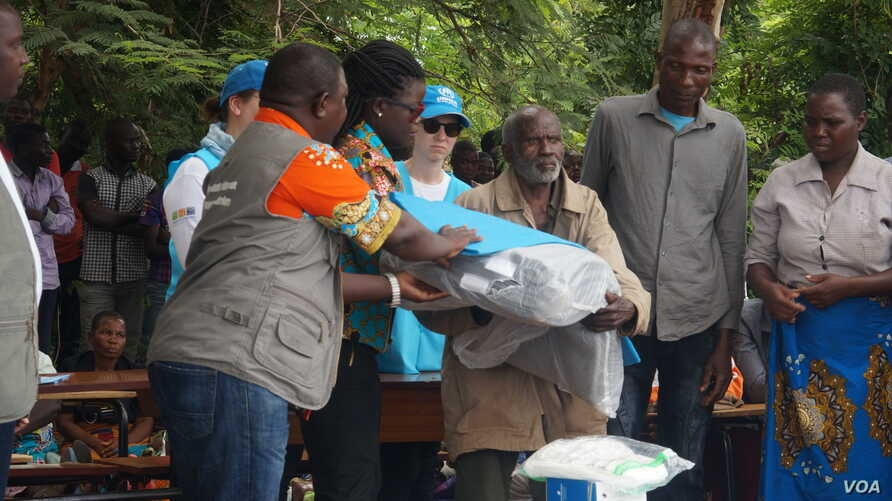 Elderly flood survivors receive assistance in the form of blankets, plastic mats, solar flashlights and other items, in Phalombe district, Malawi.