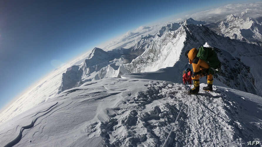 FILE - Mountaineers make their way to the summit of Mount Everest, as they ascend on the south face from Nepal, May 17, 2018.
