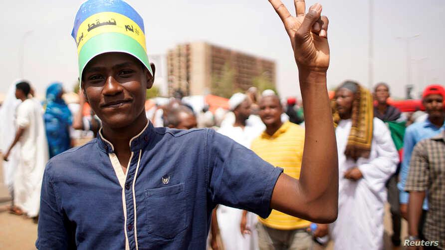A Sudanese demonstrator flashes victory sign during a protest against the army's announcement that President Omar al-Bashir would be replaced by a military-led transitional council, in Khartoum, Sudan, April 12, 2019.