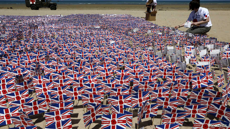FILE - Royal British Legion volunteers plant some of 22,000 Union Jack flags, adorned with picture of a poppy and hand-written notes of gratitude to Allied soldiers, on the beach in Asnelles, Normandy, France, June 6, 2014.