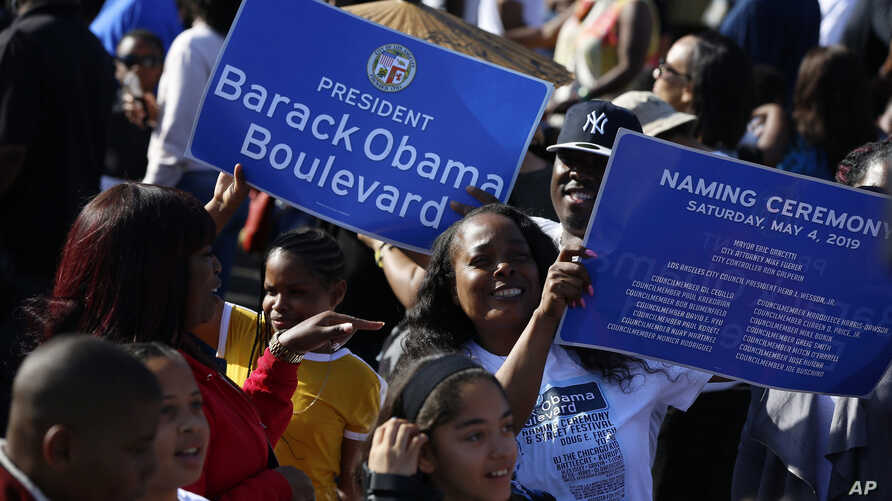 Citizens hold banners of a Obama Boulevard sign in Los Angeles, May 4, 2019. The Obama Boulevard will replace Rodeo Road, a 3 ½-mile street that runs across the city's historic black neighborhood.