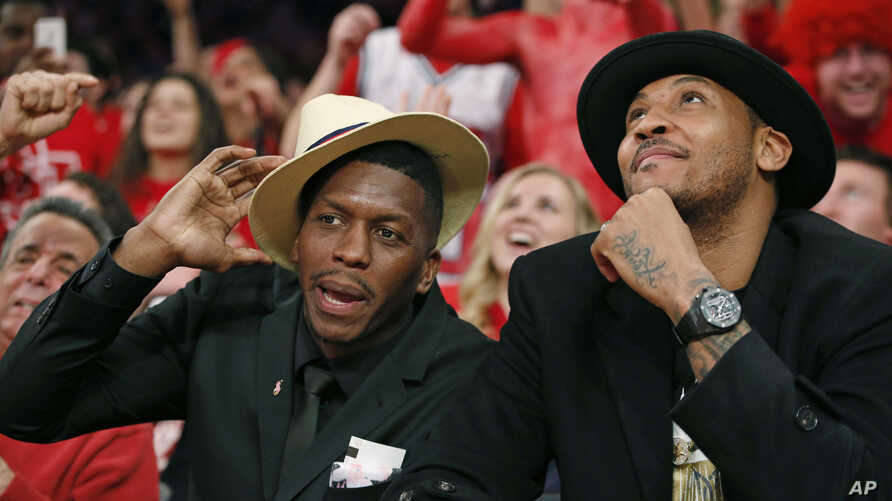FILE - Former St. Johns and NBA basketball player Felipe Lopez (L) sits beside then-New York Knicks forward Carmelo Anthony to watch the first half of an NCAA college basketball game in New York, Jan. 25, 2015.