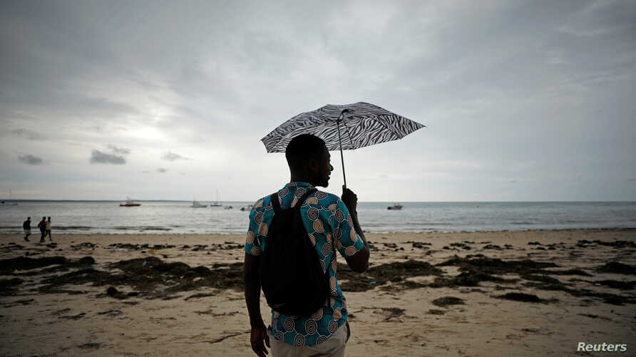 A man holds an umbrella beneath storm clouds over Wimbe beach, as the region braces for further rainfall in the aftermath of Cyclone Kenneth in Pemba, Mozambique, April 27, 2019.