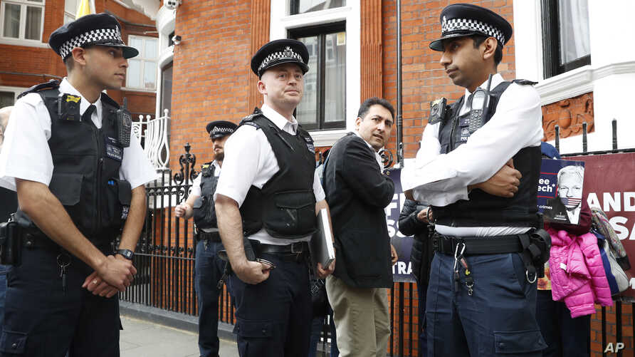 British police arrive and guard the Ecuadorian Embassy as protesters in support of Wikileaks founder Julian Assange demonstrate outside the embassy in London, May 20, 2019.