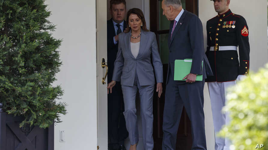 FILE - Speaker of the House Nancy Pelosi of Calif., and Senate Minority Leader Sen. Chuck Schumer of N.Y., walk out of the White House after meeting with President Donald Trump about infrastructure, April 30, 2019, in Washington.