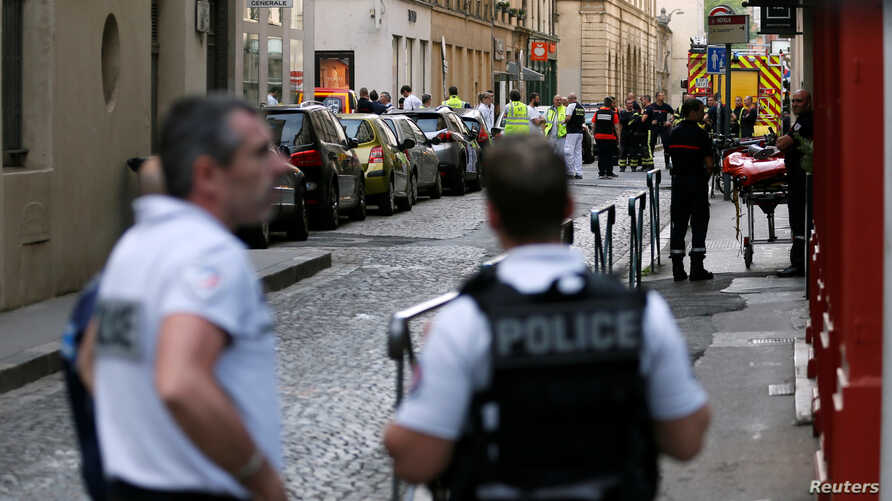 Police officers, fire fighters and medics are seen near the site of a suspected bomb attack in central Lyon, France May 24, 2019.