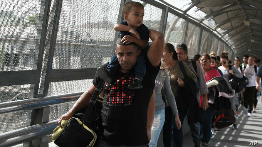 FILE - In this April 29, 2019, photo, Cuban migrants are escorted by Mexican immigration officials in Ciudad Juarez, Mexico, as they cross the Paso del Norte International bridge to be processed as asylum seekers on the U.S. side of the border.
