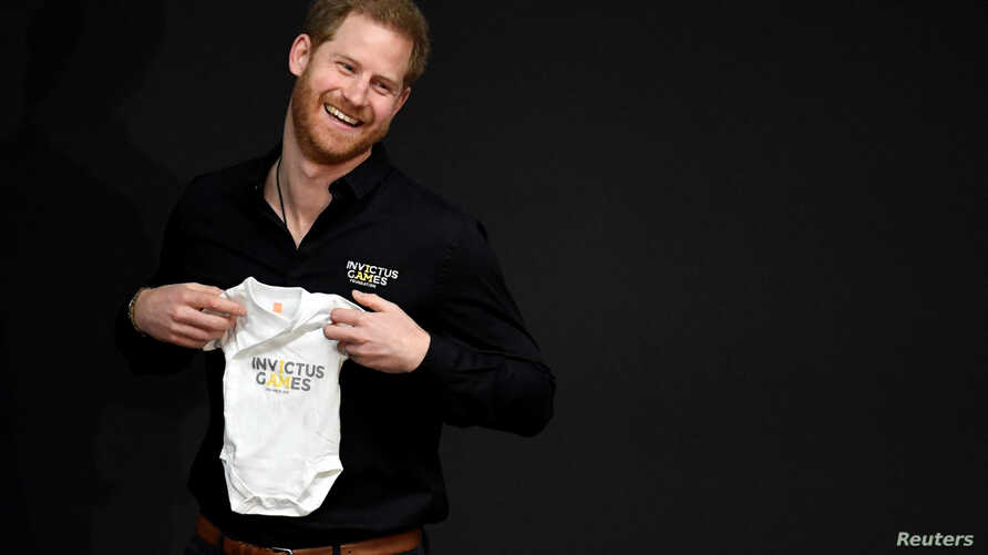Britain's Prince Harry holds a baby suit during the official launch of the one year countdown to the Invictus Games The Hague 2020, in The Hague, Netherlands, May 9, 2019.