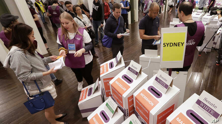 Voters cast their ballots at the Town Hall in Sydney, Australia, in a federal election, May 18, 2019. Polling stations have opened in eastern Australia on Saturday in elections that are likely to deliver the nation's sixth prime minister in as many y...