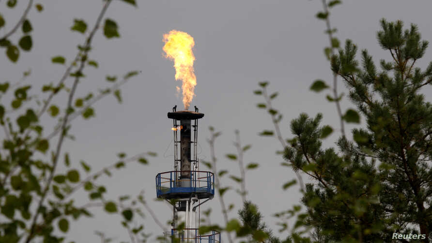 A flame burning natural gas is seen at an oil refinery located on a branch of the Druzhba oil pipeline, which moves crude through the pipeline westwards to Europe, near Mozyr, some 300 km (186 miles) southeast of Minsk, Belarus, Sept. 11, 2013.