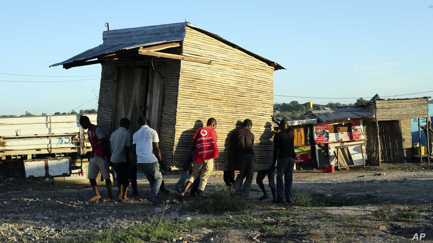 Men carry a mobile shop to safer ground in Pemba city on the northeastern coast of Mozambique, April, 27, 2019. Authorities are urging people to move immediately to higher ground as flooding and mudslides are feared in the wake of Cyclone Kenneth.