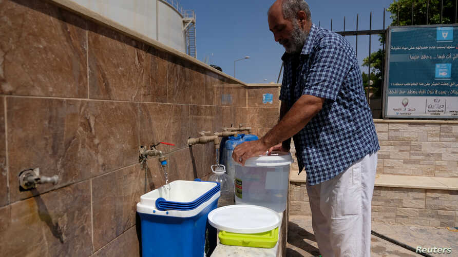A man fills jerrycans with water due to lack of water after forces loyal to Libyan commander Khalifa Haftar took control of the area, in Derna, Libya June 13, 2018.