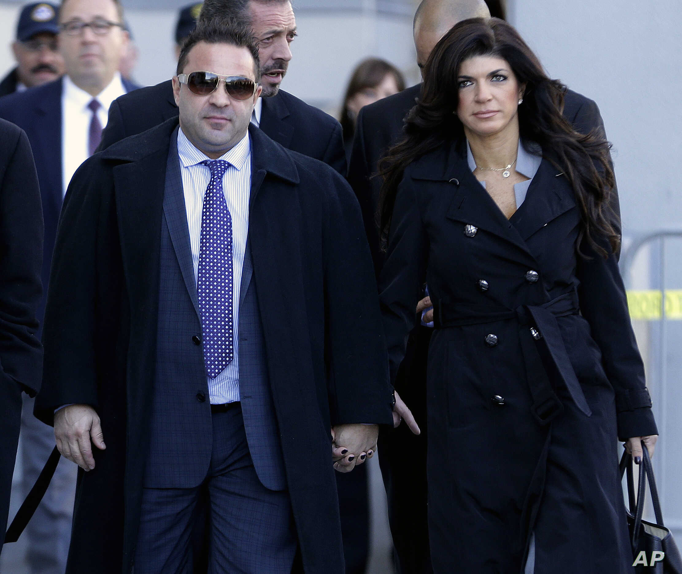 """FILE - Giuseppe """"Joe"""" Giudice, left, and his wife, Teresa Giudice, of Montville Township, N.J., walk out of Martin Luther King Jr. Courthouse after a court appearance, in Newark, N.J., Nov. 20, 2013."""