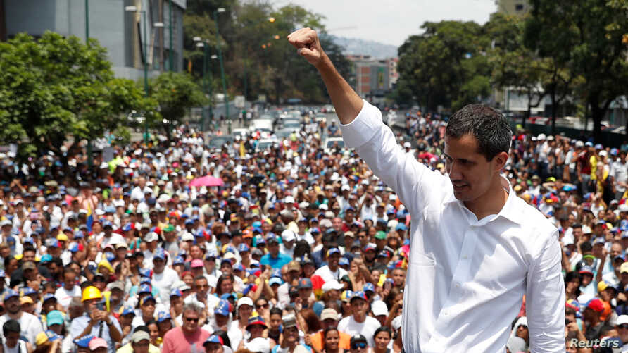 Venezuelan opposition leader Juan Guaido, whom many nations have recognized as the country's rightful interim ruler, gestures as he speaks to supporters during a rally against the government of President Nicolas Maduro and to commemorate May Day in C...