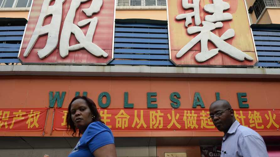 FILE - An African man and woman walk outside a clothing wholesale market in Guangzhou, China, Aug. 26, 2013.