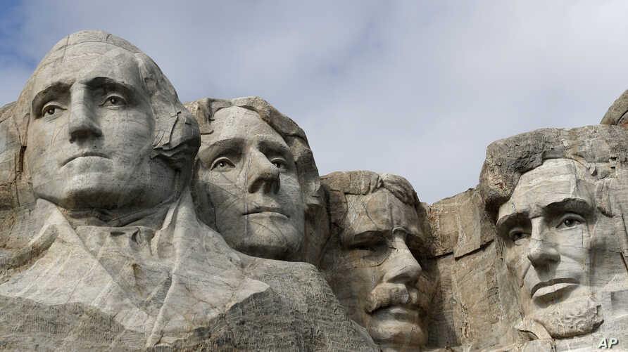 FILE - A raptor flies over Mount Rushmore on March 22, 2019, in Keystone, S.D. From left are former presidents George Washington, Thomas Jefferson, Theodore Roosevelt and Abraham Lincoln.