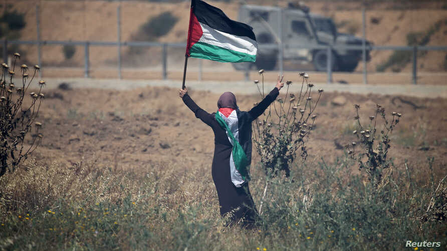 A woman holding a Palestinian flag gestures in front of Israeli forces during a protest marking the 71st anniversary of the 'Nakba', or catastrophe, at the Israel-Gaza border fence, in the southern Gaza Strip, May 15, 2019.