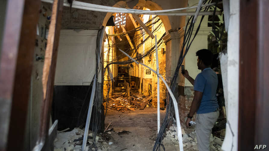 A Sri Lankan man uses his mobile phone to take pictures inside St. Anthony's Shrine in Colombo on April 26, 2019, following a series of bomb blasts targeting churches and luxury hotels on Easter Sunday in Sri Lanka.