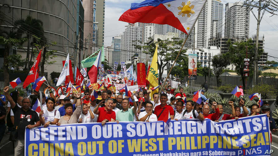 """Hundreds of protesters march for a rally towards the Chinese Consulate to coincide with the country's commemoration of """"Araw Ng Kagitingan"""" (Day of Valor) Tuesday, April 9, 2019 in suburban Makati city, east of Manila, Philippines. The protesters are calling on the citizenry to uphold national sovereignty in the wake of China's alleged continued occupation of the disputed islands, shoals and reefs in the South China Sea as well as President Rodrigo Duterte's alleged """"warmer ties with China."""" (AP Photo/Bulli"""