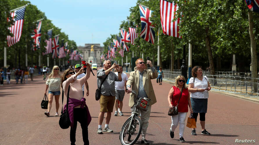 People photograph workers putting up U.S. flags along The Mall towards Buckingham Palace in central London ahead of U.S. President Donald Trump state visit to Britain, London, Britain, June 2, 2019.