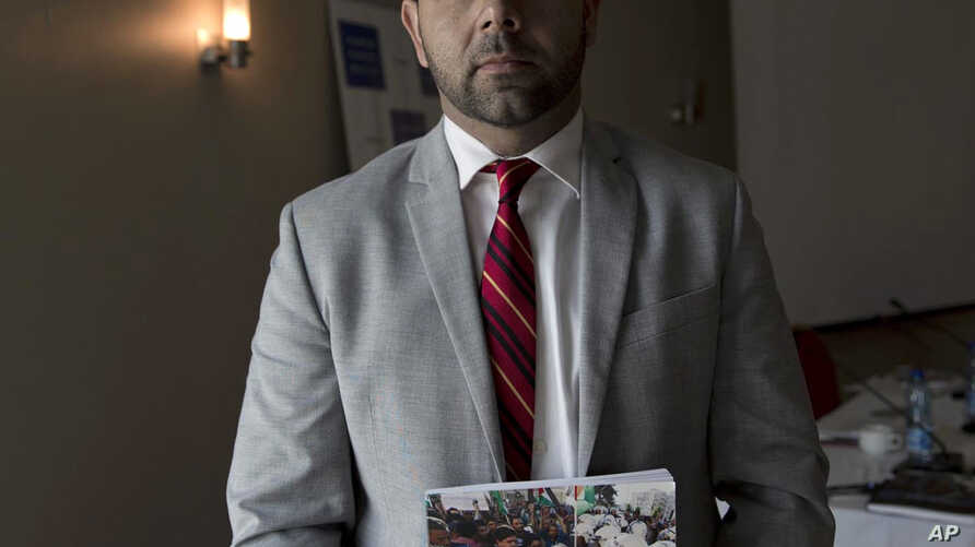 Omar Shakir, Israel and Palestine Director of the New York-based Human Rights Watch, poses with a copy of a report released Tuesday following a two year investigation, in the West Bank city of Ramallah, Tuesday, Oct. 23, 2018.