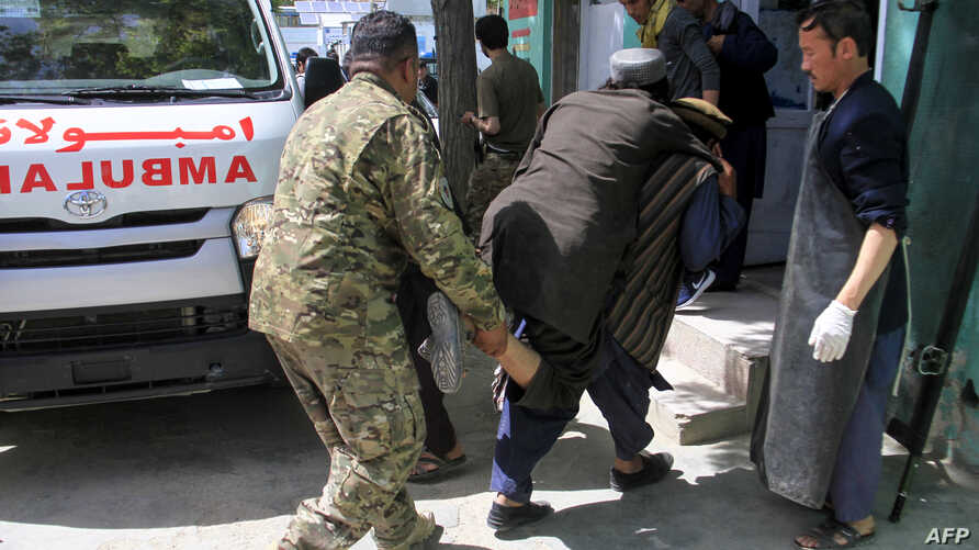 Afghan security personnel and voluntaries carry an injured man to a hospital following a suicide bomber attack with explosives packed in a vehicle in Ghazni province on May 22, 2019.