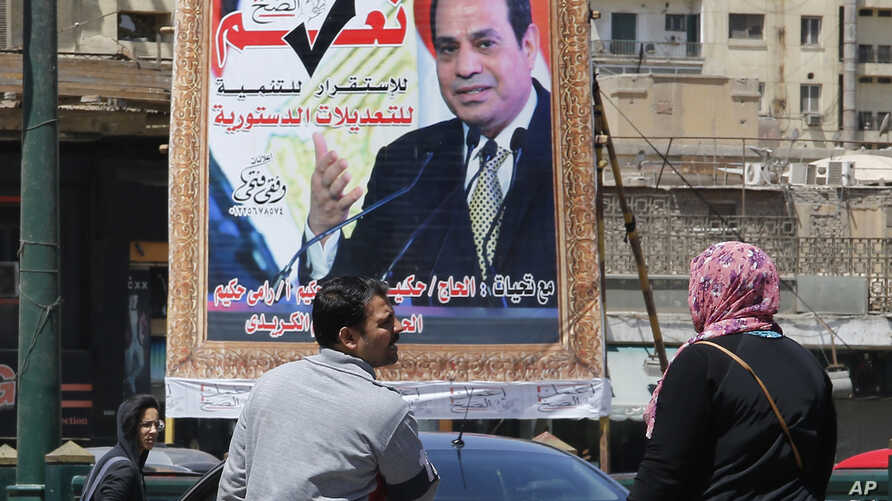 People walk past a banner supporting proposed amendments to the Egyptian constitution on new term limits, with a poster of Egyptian President Abdel-Fattah el-Sissi in Cairo, Egypt, April 16, 2019.