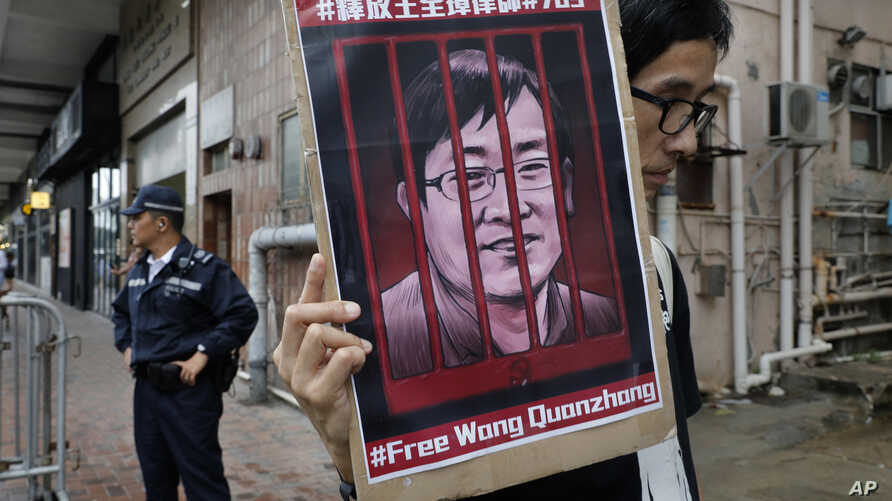 FILE - A protester holds a picture of imprisoned and prominent Chinese human rights lawyer Wang Quanzhang during a protest outside the Chinese liaison office in Hong Kong, July 13, 2018.