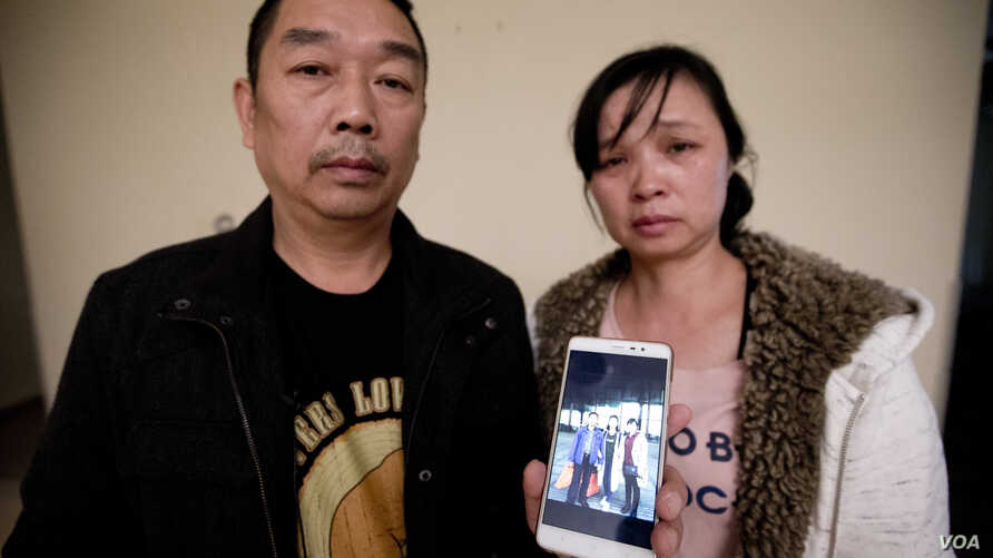 FILE - Ronggao Zhang, left, and Lifeng Ye, hold a photo of  their missing daughter, Yingying Zhang, in Urbana, Ill., Nov. 1, 2017.