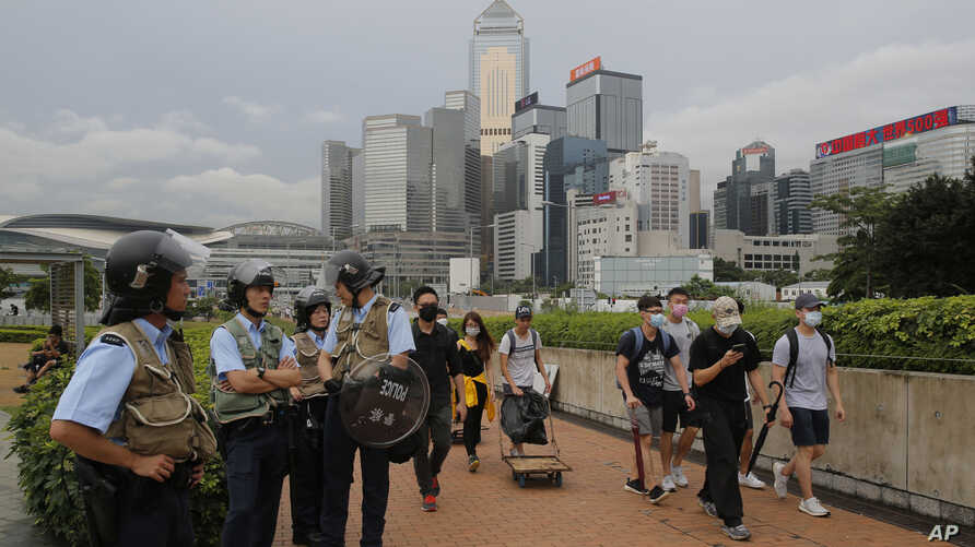 Riot police stand guard as protesters walk outside the Legislative Council in Hong Kong, June 13, 2019.
