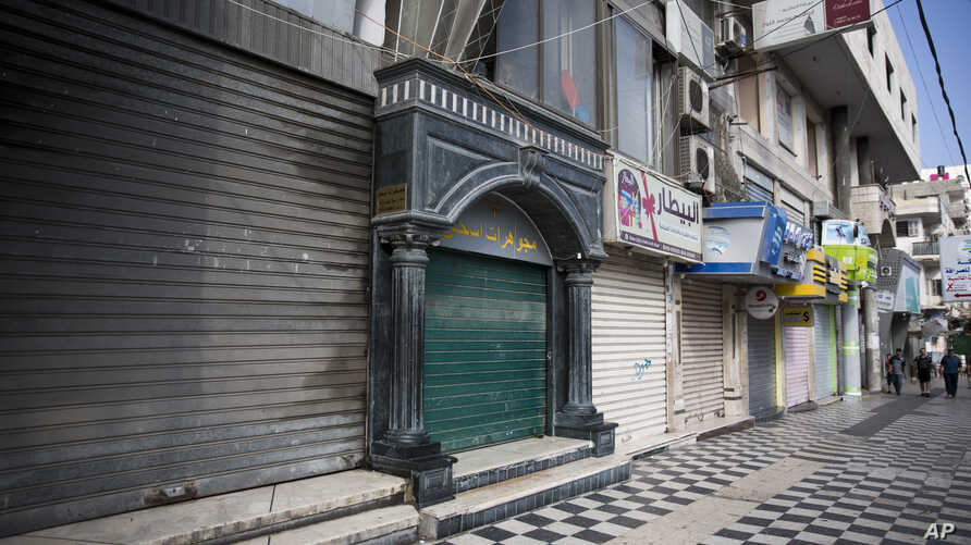 Palestinians walk next to closed shops in Gaza City, Tuesday, June 25, 2019, during a general strike against this week's economic conference in Bahrain that will kick off the Trump administration's plan for Mideast peace.