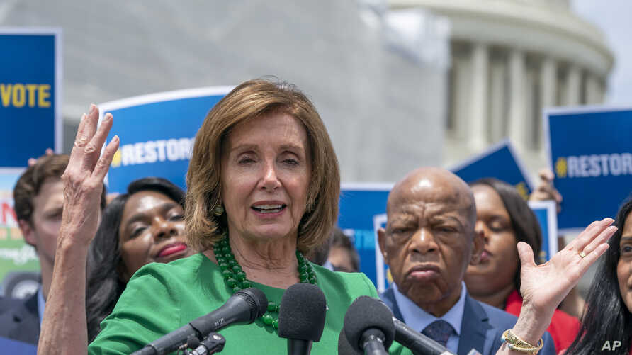 Speaker of the House Nancy Pelosi, D-Calif., flanked by Rep. Terri Sewell, D-Ala., left, and Rep. John Lewis, D-Ga., right, talks to reporters on Capitol Hill.