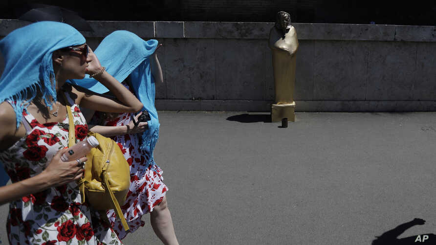 Tourists wear a scarf over their head to protect themselves from the sun as they walk past a street performer impersonating an Egyptian sphinx, in Rome, Thursday, June 27, 2019.