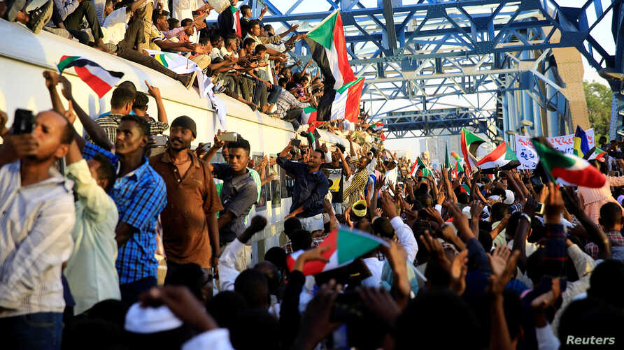 Sudanese demonstrators welcome a train carrying protesters from Atbara, the birthplace of an uprising that toppled Sudanese former President Omar al-Bashir, as they approach the military headquarters in Khartoum, April 23, 2019.