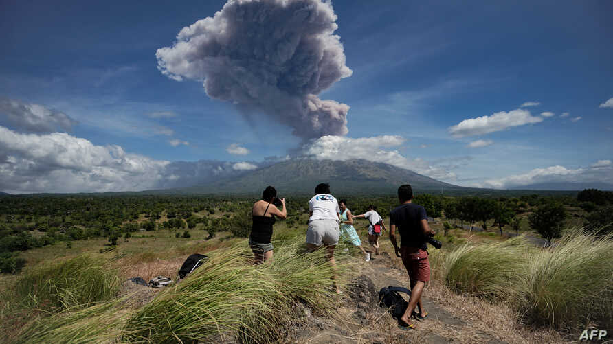 A plume of ash is released as Mount Agung volcano erupts, seen from the Kubu subdistrict in Karangasem Regency on Indonesia's resort island of Bali on May 31, 2019.
