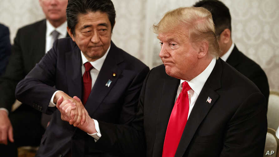 President Donald Trump, right, and Japanese Prime Minister Shinzo Abe shake hands during a meeting with Japanese families of those abducted by North Korea, at Akasaka Palace, Monday, May 27, 2019, in Tokyo.